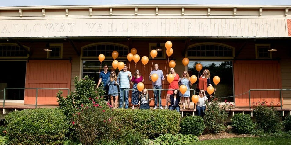 Mostly Serious team members holding orange balloons outside their new office at 4064 S. Lone Pine
